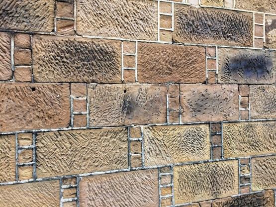 """A faragott homokkő téglák. Ha türelmesen keresgélünk találhatunk hasonló mintázatú köveket. Na nem ezen a képen, hanem az egész homlokzaton. Nekünk sikerült. És jól látszanak kisebb kövekből alkotott """"létra"""" minta is."""